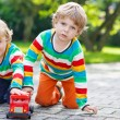 Two siblings, kid boys playing with red school bus — Stock Photo #55584023