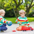 Two siblings, kid boys playing with red school bus — Stock Photo #55584225