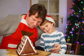 Father and little son preparing a gingerbread cookie house — 图库照片