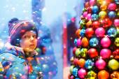 Adorable little boy looking through the window at Christmas deco — Stock Photo