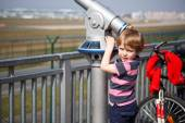 Little blond boy watching airplanes in observation tube on airpo — Stock Photo