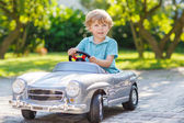Little boy driving big toy old car, outdoors — Stockfoto