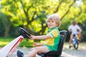 Активный мальчик педали на автомобиле, в летнем саду — Стоковое фото
