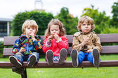 Two little boys and one girl eating chocolate — Stock Photo