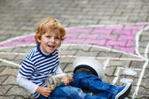 Little boy having fun with ship picture drawing with chalk — Stock Photo
