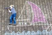 Little boy having fun with ship picture drawing with chalk — Foto de Stock