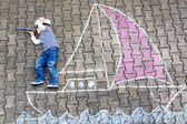Little boy having fun with ship picture drawing with chalk — Stockfoto