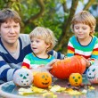 Young father and two little sons making jack-o-lantern for hallo — Stock Photo #55998981