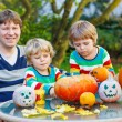 Young father and two siblings making jack-o-lantern for hallowee — Stock Photo #55999049