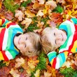 Two little kid boys laying in autumn leaves in colorful clothing — Stock Photo #56403739