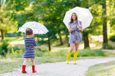 Happy mother and her little cute kid girl in rain boots — 图库照片