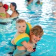 Little baby boy and his mother learning to swim in an indoor swi — Stock Photo #57123543
