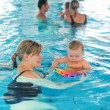 Little baby boy and his mother learning to swim in an indoor swi — Stock Photo #57123567