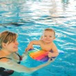 Little baby boy and his mother learning to swim in an indoor swi — Stock Photo #57123585
