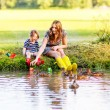 Adorable little girl and her mom playing with paper boats in a r — Stock Photo #57123979