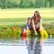 Adorable little girl and her mom playing with paper boats in a r — Stock Photo #57124075