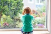 Little blond kid boy sitting near window and looking on raindrop — Stock Photo