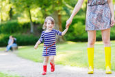 Mother and little adorable child girl in rubber boots having fun — Stock Photo