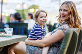 Mother and little adorable kid girl drinking coffee in outdoor c — Foto de Stock