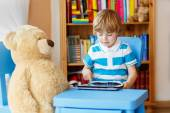 Little kid boy playing with tablet computer in his room at home — Stock Photo