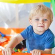 Cute little baby boy playing in colorful playpen, indoors — Stock Photo #58150951