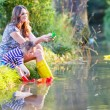 Adorable little girl and her mom playing with paper boats in a r — Stock Photo #58151451