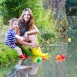 Adorable little girl and her mom playing with paper boats in a r — Stock Photo #58151537