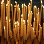 Burning church candles on dark background, christian symbol. — Stock Photo #58154045