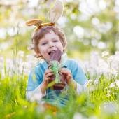 Little toddler wearing Easter bunny ears and eating chocolate at — ストック写真