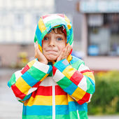 Funny smiling little boy walking in city through rain — Stockfoto