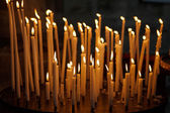 Burning church candles on dark background, christian symbol. — Stockfoto