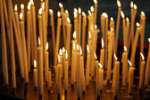 Burning church candles on dark background, christian symbol. — Stock Photo