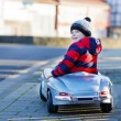 Funny little boy driving big toy car and having fun, outdoors — Stock Photo #58932743