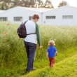 Father and little son boy walking through poppy field in summer — Stock Photo #58935521