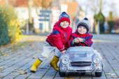 Two happy sibling boys playing with big old toy car, outdoors — Stock Photo