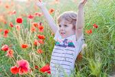 Cute kid boy with poppy flower on poppy field on warm summer day — Zdjęcie stockowe