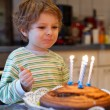 Adorable four year old boy celebrating his birthday and blowing — Stock Photo #60635345