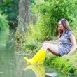Young beautiful woman sitting in yellow rain rubber boats by a r — Foto Stock #60635817
