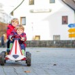 Two little friends kids in red jackets driving fast race car tog — Stock Photo #60636423