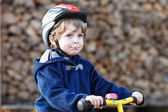 Little boy riding bicycle in village or city — Stock Photo