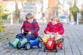 Two happy friends boys playing with colorful toy car, outdoors — Stok fotoğraf