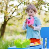 Little boy playinig with colorful eggs — Stock Photo