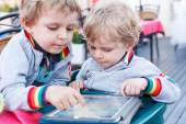 Two little sibling boys having fun together with tablet pc. — Stock Photo