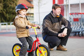Little toddler boy with bicycle and his father in the city — Stock Photo