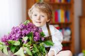 Adorable smiling little boy with blooming purple lilac flowers — Stock Photo