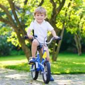 Happy preschool boy riding his first bike — Stock Photo