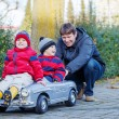 Two happy sibling boys and father playing with big old toy car, — Stock Photo #60745531