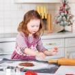 Little girl baking gingerbread cookies in domestic kitchen — Stock Photo #60745655