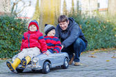 Two happy sibling boys and father playing with big old toy car,  — Stok fotoğraf