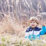 Little boy having fun with bulrush near forest lake — Stock Photo #61781719